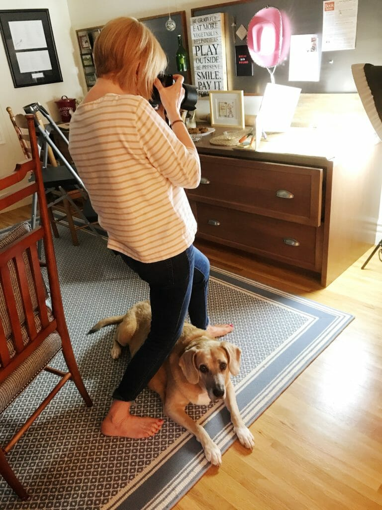 photographer with dog underfoot